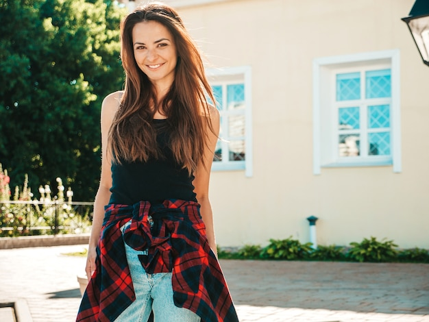 Portrait of beautiful smiling brunette model. trendy female posing in the street
