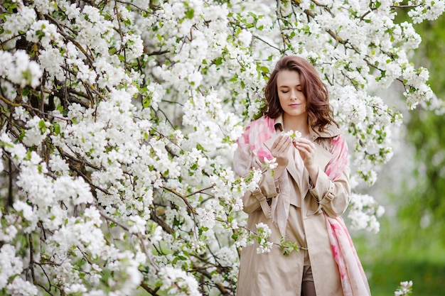 Portrait of a beautiful smiling brunette young women in blossom apple tree garden in spring time. enjoy nature. healthy girl outdoor. spring concept. beautiful girl in orchard