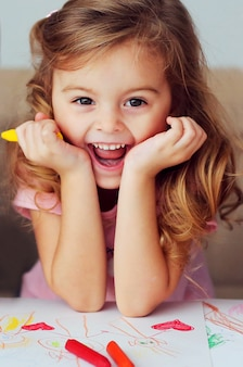 Portrait of a beautiful smiling child of european appearance with curly hair on the background of children's drawings.