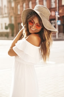 Portrait of beautiful smiling cute blond teenager model with no makeup in summer hipster white dress and big beach hat posing on the street background
