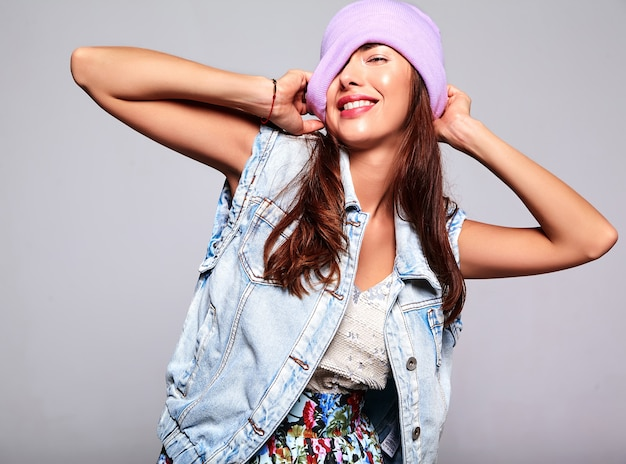 Portrait of beautiful smiling cute brunette woman model in casual summer jeans clothes with no makeup in purple beanie isolated on gray
