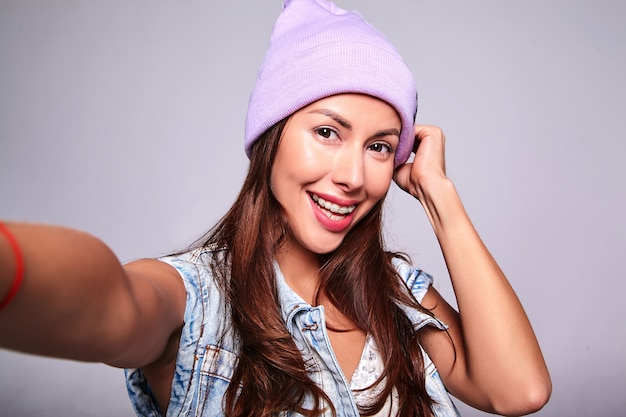 Portrait of beautiful smiling cute brunette woman model in casual summer jeans clothes with no makeup in purple beanie making selfie photo on phone isolated on gray
