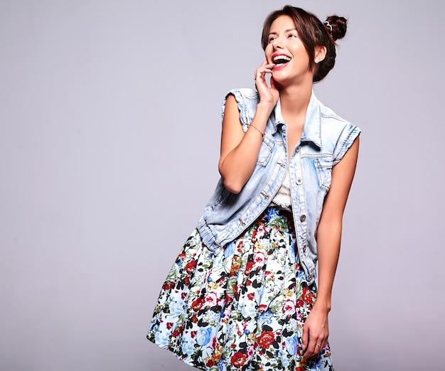 Il ritratto di bello modello sveglio sorridente della donna del brunette in jeans casuali dell'estate copre senza trucco con l'acconciatura dei corni isolata su gray