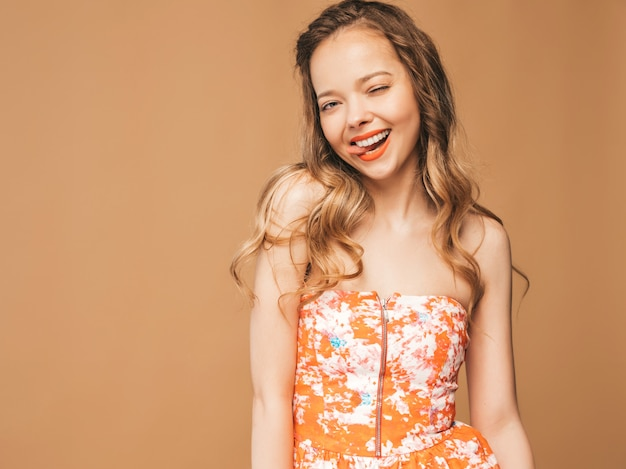 Portrait of beautiful smiling cute model with pink lips. girl in summer colorful dress. model posing.showing her tongue