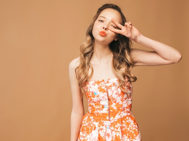 Portrait of beautiful smiling cute model with pink lips. girl in summer colorful dress. model posing.showing peace sign and giving kiss
