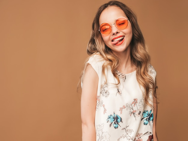 Portrait of beautiful smiling cute model with pink lips. girl in summer colorful dress and sunglasses. model posing