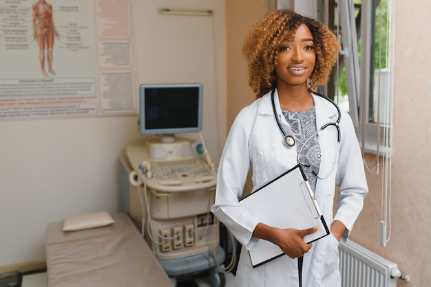 Portrait of beautiful smiling female african american doctor standing in medical office