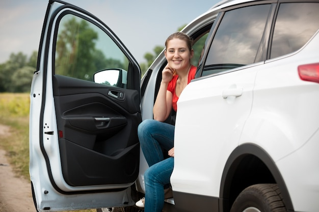 Portrait of beautiful smiling female driver relaxing in car at the field