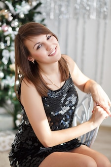 Portrait of a beautiful smiling girl in elegant christmas decorations