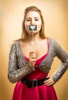 Portrait of beautiful smiling girl holding sign with drawn heart at lips