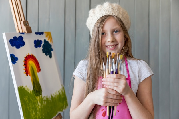 Portrait of a beautiful smiling girl wearing knit cap holding various type of brushes standing near the canvas