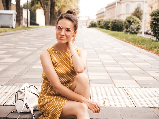 Portrait of beautiful smiling hipster model dressed in summer yellow dress. trendy girl posing in the street. funny and positive woman having fun