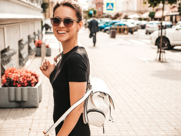 Portrait of beautiful smiling model dressed in summer clothes. trendy girl posing in the street in sunglasses. funny and positive woman having fun