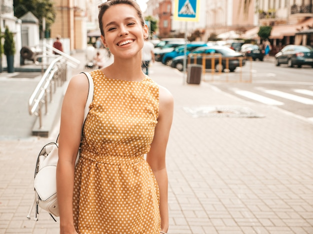 Portrait of beautiful smiling model dressed in summer yellow dress. trendy girl posing in the street. funny and positive woman having fun