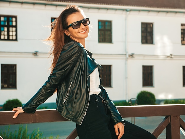 Portrait of beautiful smiling model. female dressed in summer hipster black leather jacket and jeans. she posing on the street