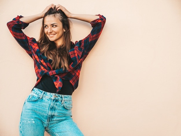 Portrait of beautiful smiling model. female dressed in summer hipster checkered shirt and jeans. trendy girl posing near wall in the street