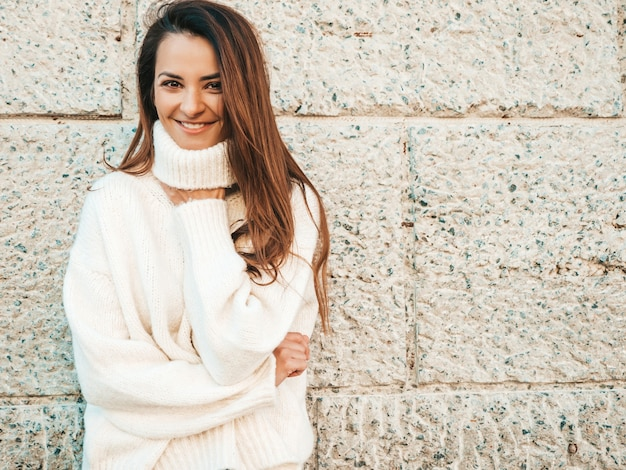Portrait of beautiful smiling model. female dressed in warm hipster white sweater. posing near wall in the street