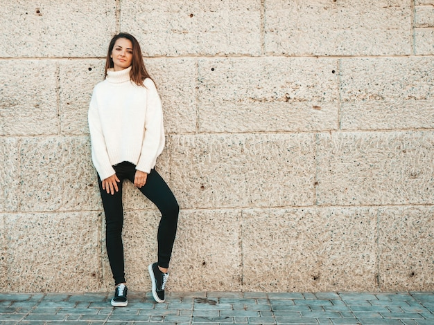 Portrait of beautiful smiling model. female dressed in warm hipster white sweater. trendy girl posing near wall in the street
