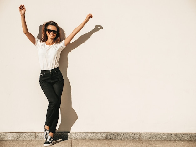 Portrait of beautiful smiling model in sunglasses. female dressed in summer hipster white t-shirt and jeans.posing near wall in the street