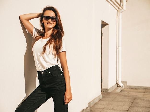 Ritratto di bella modella sorridente in occhiali da sole. donna vestita di maglietta e jeans bianchi hipster estivi. ragazza alla moda in posa vicino al muro in strada