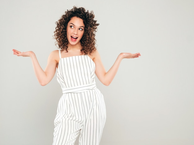 Portrait of beautiful smiling model with afro curls hairstyle dressed in summer hipster clothes.sexy carefree girl displaying something on both flat hands for similar choice of product
