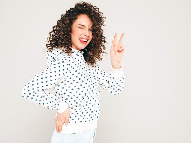 Portrait of beautiful smiling model with afro curls hairstyle dressed in summer hipster clothes.sexy carefree girl posing on gray backgroundl.trendy funny and positive woman in white hoodie