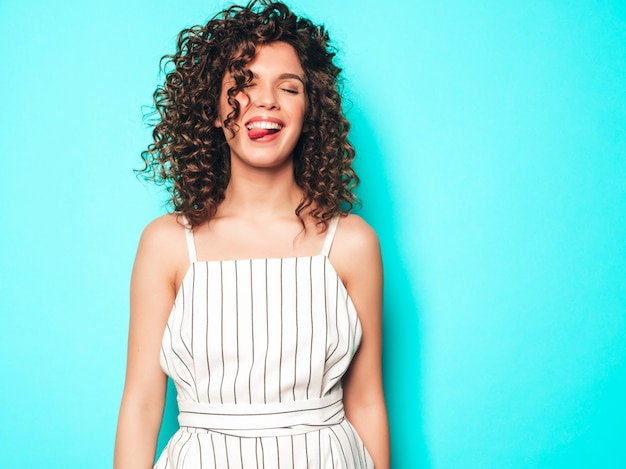 Portrait of beautiful smiling model with afro curls hairstyle dressed in summer hipster clothes.sexy carefree girl posing near blue wall.trendy funny and positive woman.shows tongue
