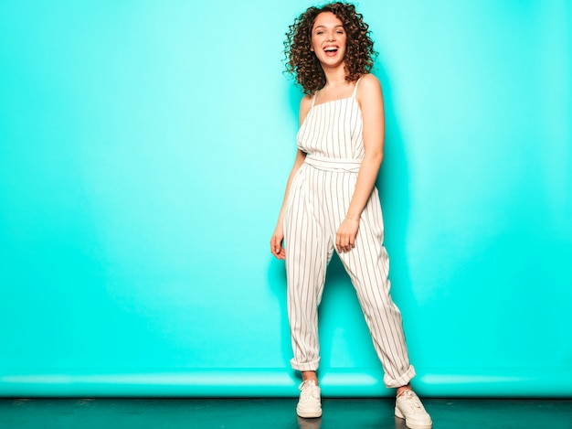 Portrait of beautiful smiling model with afro curls hairstyle dressed in summer hipster clothes.sexy carefree girl posing near blue wall.trendy funny and positive woman