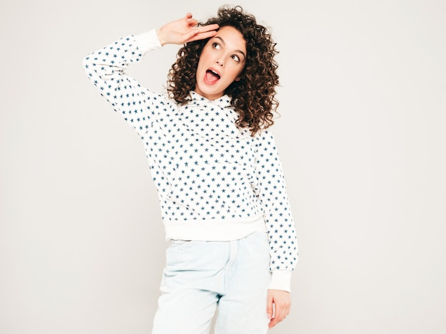 Portrait of beautiful smiling model with afro curls hairstyle dressed in summer hipster clothes.sexy carefree girl posing in studio on gray background.trendy funny and positive woman