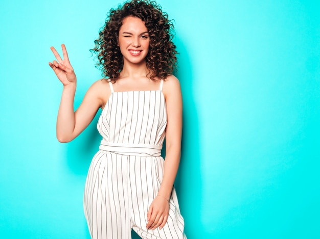 Portrait of beautiful smiling model with afro curls hairstyle dressed in summer hipster clothes.trendy funny and positive woman shows peace sign