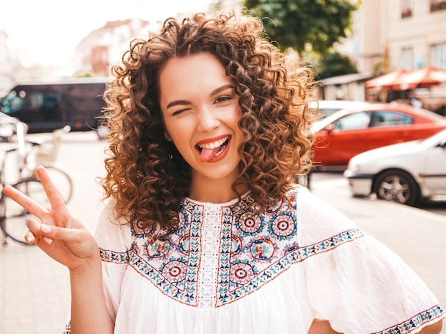 Portrait of beautiful smiling model with afro curls hairstyle dressed in summer hipster white dress