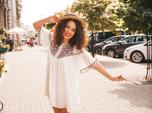 Portrait of beautiful smiling model with afro curls hairstyle dressed in summer hipster white dress.