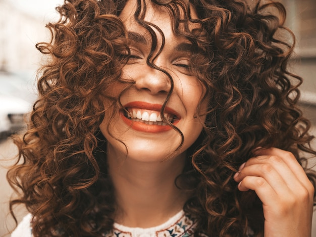 Portrait of beautiful smiling model with afro curls hairstyle.