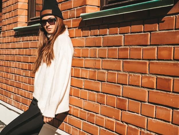 Ritratto di bella modella sorridente. donna vestita di caldo maglione bianco hipster e berretto. lei posa per strada