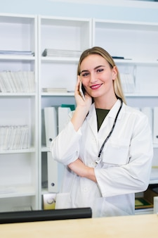 Portrait of a beautiful smiling nurse at desk station while talking on the phone and complete a medical information form