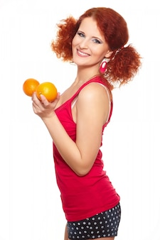 Ritratto di bella donna sorridente dello zenzero di redhead in panno rosso isolato su bianco con l'arancia