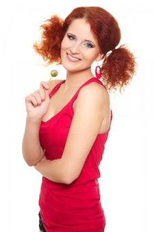 Portrait of beautiful smiling redhead ginger woman in red cloth with sweet isolated on white