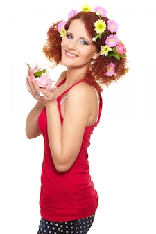 Portrait of beautiful smiling redhead ginger woman in red cloth with yellow pink colorful flowers in hair isolated on white holding flowers