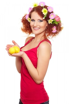 Portrait of beautiful smiling redhead ginger woman in red cloth with yellow pink colorful flowers in hair isolated on white with lemon in hands