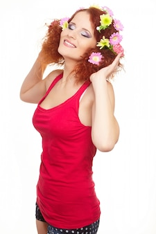Portrait of beautiful smiling redhead ginger woman in red cloth with yellow pink colorful flowers in hair isolated on white