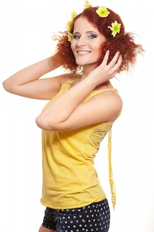 Portrait of beautiful smiling redhead ginger woman in yellow cloth with yellow flowers in hair isolated on white