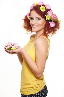 Portrait of beautiful smiling redhead ginger woman in yellow cloth with yellow pink colorful flowers in hair isolated on white holding flowers