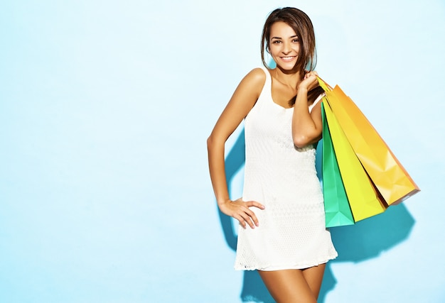 Portrait of beautiful smiling shopaholic woman holding colorful paper bags. brunette woman posing on blue wall after shopping. positive model
