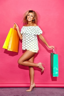 Portrait of beautiful smiling shopaholic woman holding colorful paper bags
