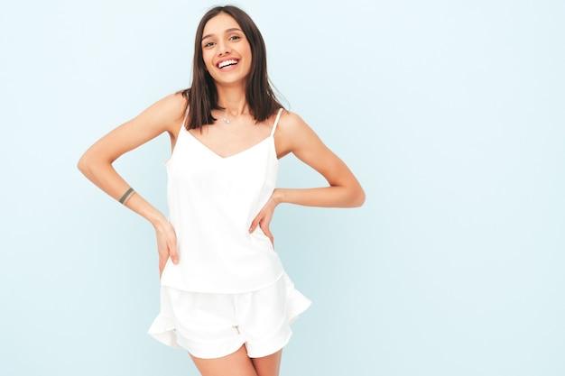 Ritratto di bella donna sorridente vestita di pigiama bianco.