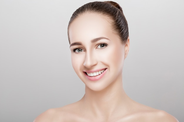 Portrait of beautiful smiling woman on grey background closeup. girl with clean skin