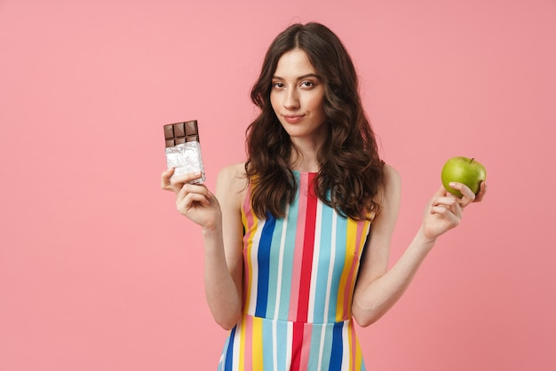 Portrait of beautiful smiling woman posing isolated over pink wall holding apple and chocolate