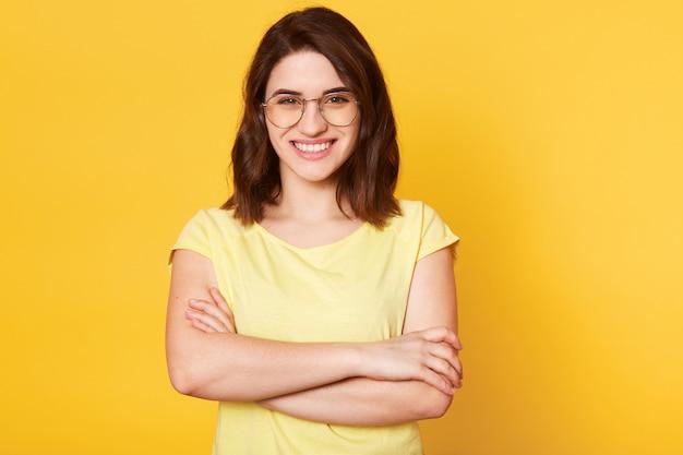 Ritratto di bella donna sorridente con le mani piegate isolato su studio giallo