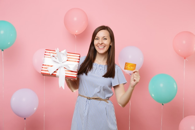 Portrait of beautiful smiling young woman in blue dress holding credit card and red box with gift present on pink background with colorful air balloon. birthday holiday party, people sincere emotions.