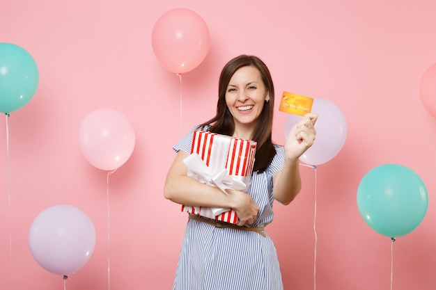 Portrait of beautiful smiling young woman in blue dress holding credit card and red box with gift present on pink background with colorful air balloons. birthday holiday party, people sincere emotion.